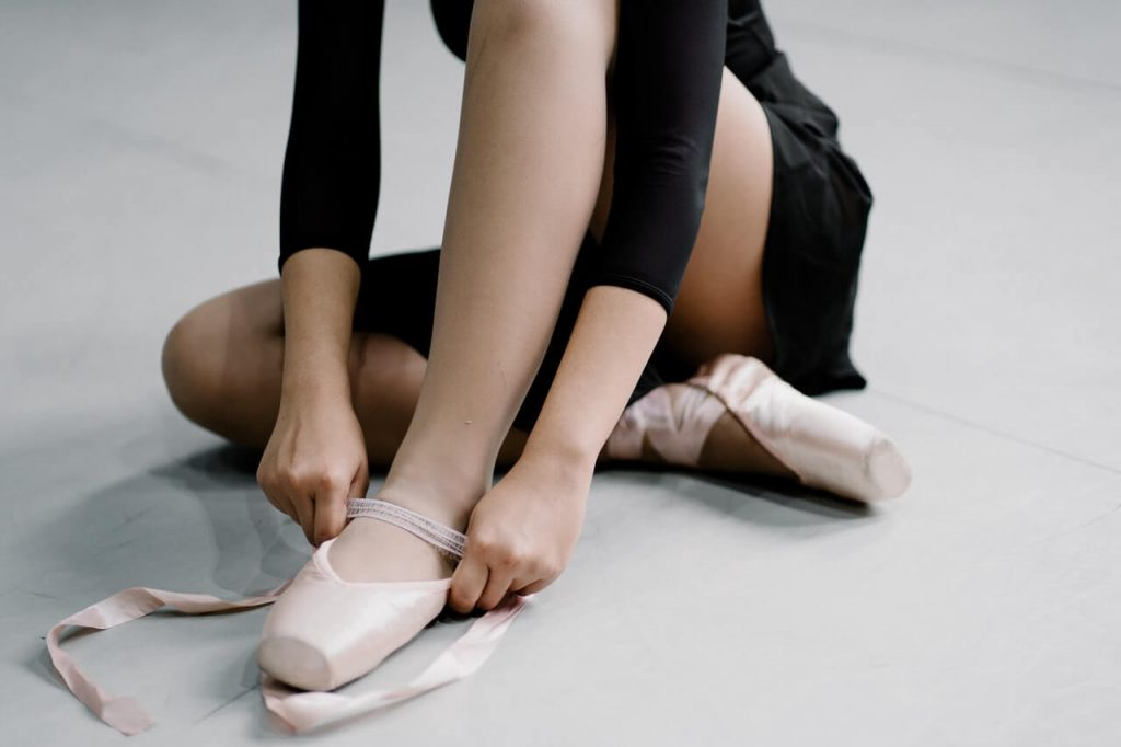 Toddler putting on ballet shoes